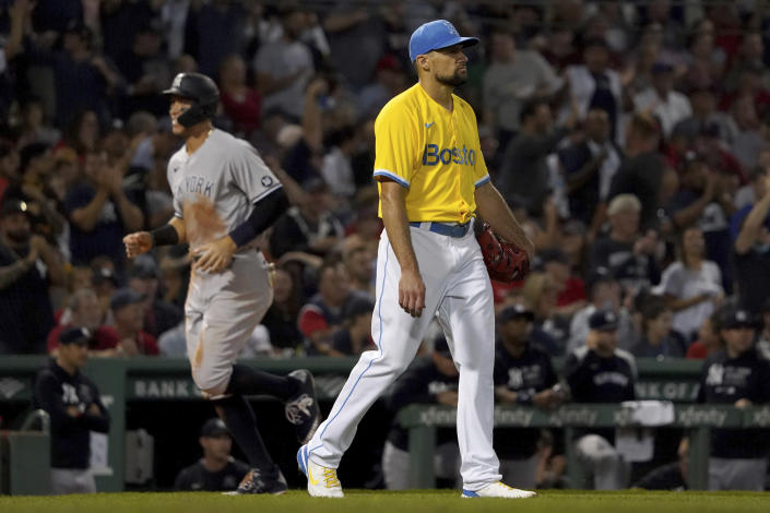 Boston Red Sox starting pitcher Nathan Eovaldi, right, reacts after giving up a three-run home run to New York Yankees designated hitter Giancarlo Stanton (not shown) as Aaron Judge, left, rounds the bases to score during the third inning of a baseball game at Fenway Park, Friday, Sept. 24, 2021, in Boston. (AP Photo/Mary Schwalm)