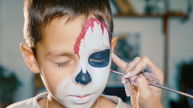 Make-up artist makes the boy halloween make up. Halloween child face art. Drawing skull body art for halloween party.