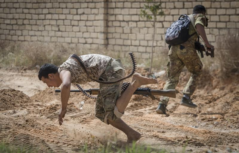 Libyan fighters loyal to the internationally recognised Government of National Accord (GNA) run for cover during clashes forces of strongman Khalifa Haftar south of the capital Tripoli