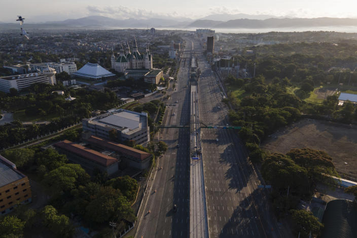 Mountain ranges can be seen behind an almost empty Commonwealth Avenue as the government implements a strict lockdown to prevent the spread of the coronavirus on Good Friday, April 2, 2021 in Quezon city, Philippines. Filipinos marked Jesus Christ's crucifixion Friday in one of the most solemn holidays in Asia's largest Catholic nation which combined with a weeklong coronavirus lockdown to empty Manila's streets of crowds and heavy traffic jams. Major highways and roads were eerily quiet on Good Friday and churches were deserted too after religious gatherings were prohibited in metropolitan Manila and four outlying provinces. (AP Photo/Aaron Favila)