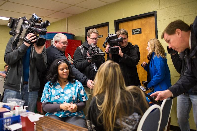 Members of the media surround a family as their child is screened for lead exposure at Eisenhower Elementary School in Flint, Michigan (AFP Photo/Brett Carlsen)