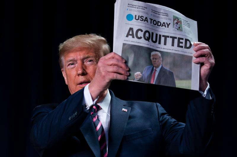 """Donald Trump brandishes a newspaper with the banner headline """"Acquitted"""" at the National Prayer Breakfast in Washington, a day after the Senate impeachment trial ended: AP"""