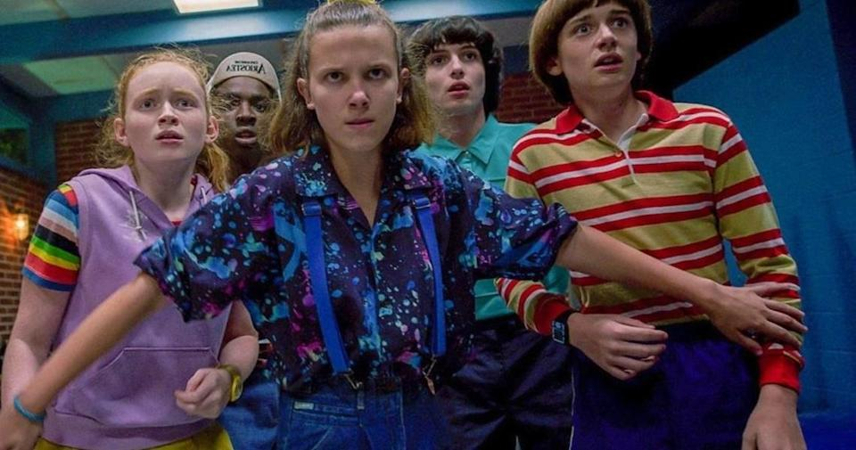 Millie Bobbie Brown stands protectively in front of four other kids