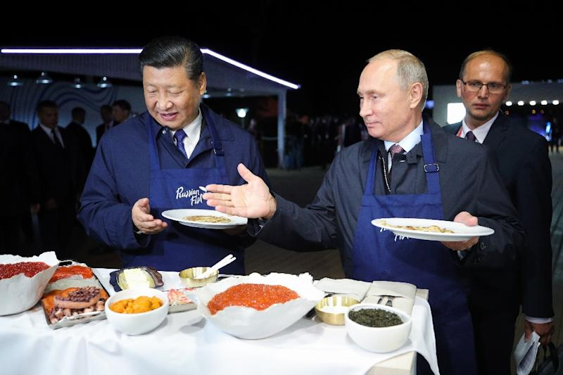 Russian President Vladimir Putin and his Chinese counterpart Xi Jinping found time to flip pancakes (AFP Photo/Sergei BOBYLYOV)