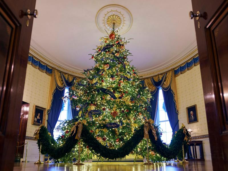 The 18-foot-tall official White House Christmas tree, draped in over 500 feet of blue velvet ribbon embroidered in gold with each state and territory, is seen in the Blue Room on Nov. 26, 2018.
