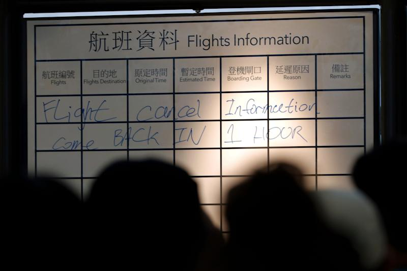 Travelers gather near a flights information board at the Hong Kong International airport.