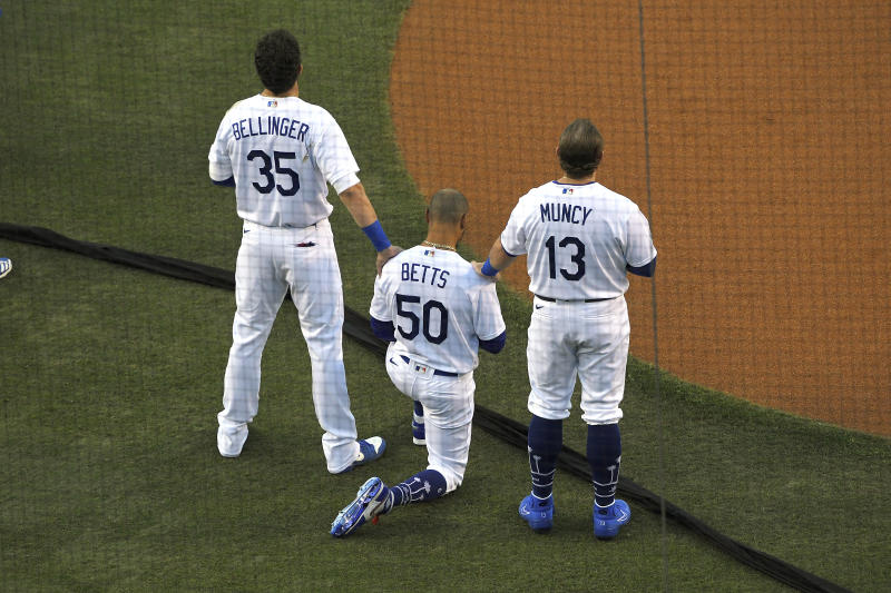 Los Angeles Dodgers' Cody Bellinger, left, and Max Muncy, right, put their hands on Mookie Betts during the national anthem prior to an opening day baseball game Thursday, July 23, 2020, in Los Angeles. (AP Photo/Mark J. Terrill)