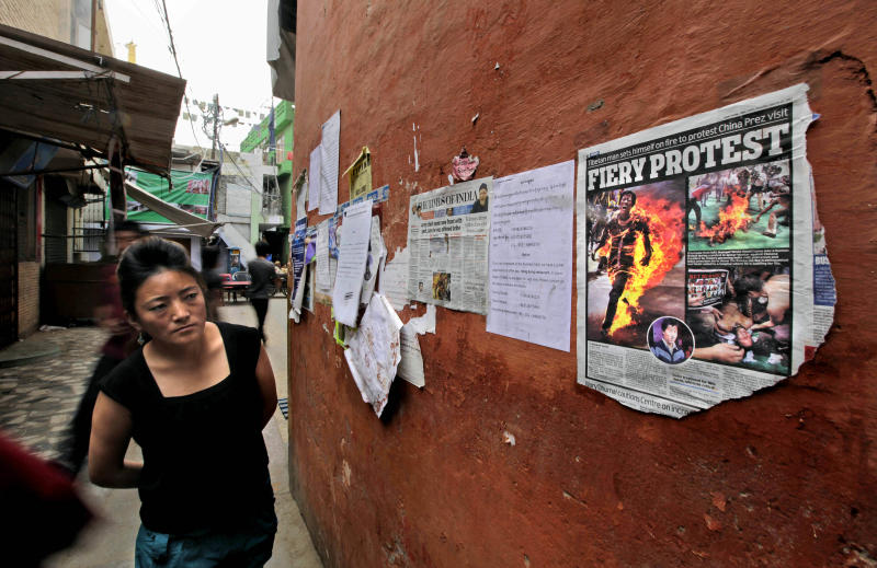 An exile Tibetan woman looks at a newspaper page with photos of Tibetan Jampa Yeshi who immolated himself Monday during a protest, at a Tibetan Refugee settlement in New Delhi, India, Tuesday, March 27, 2012. Yeshi, who remains in critical condition after he lit himself on fire and ran shouting through a protest in the Indian capital Monday, just ahead of a visit by China's president Hu Jintao for an economic summit this week. (AP Photo/Altaf Qadri)