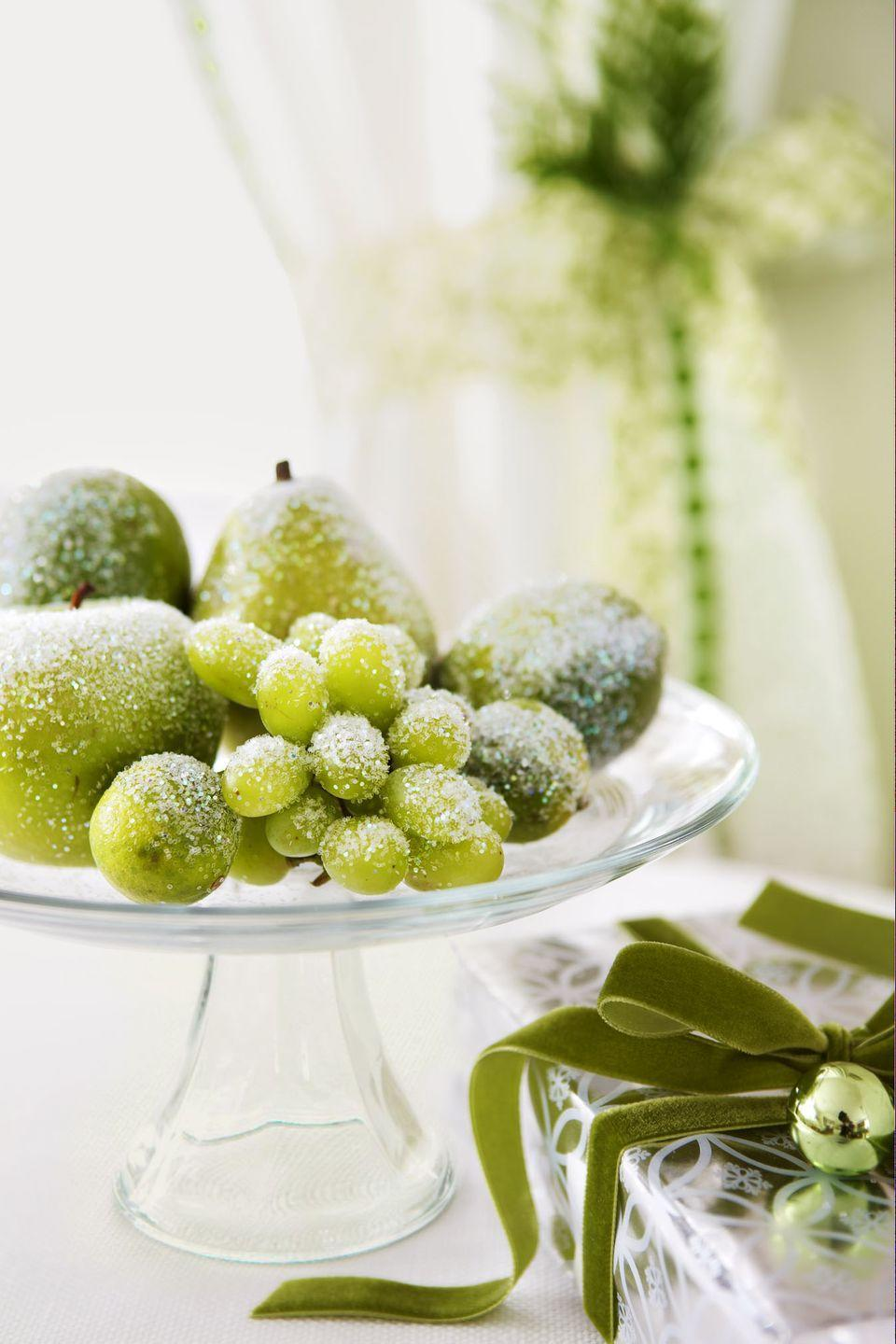 """<p>Faux grapes, limes, and pears dusted with glitter look plucked from Jack Frost's icy orchard — and will last for years. (To craft, coat fruit with spray adhesive and roll in a mixture of three parts white glitter to one part silver glitter.</p><p><span class=""""redactor-invisible-space""""><a class=""""link rapid-noclick-resp"""" href=""""https://www.amazon.com/Gresorth-Artificial-Lifelike-Simulation-Decoration/dp/B00MNBJ2EO/?tag=syn-yahoo-20&ascsubtag=%5Bartid%7C10055.g.2196%5Bsrc%7Cyahoo-us"""" rel=""""nofollow noopener"""" target=""""_blank"""" data-ylk=""""slk:SHOP FAUX PEARS"""">SHOP FAUX PEARS</a></span><br></p>"""