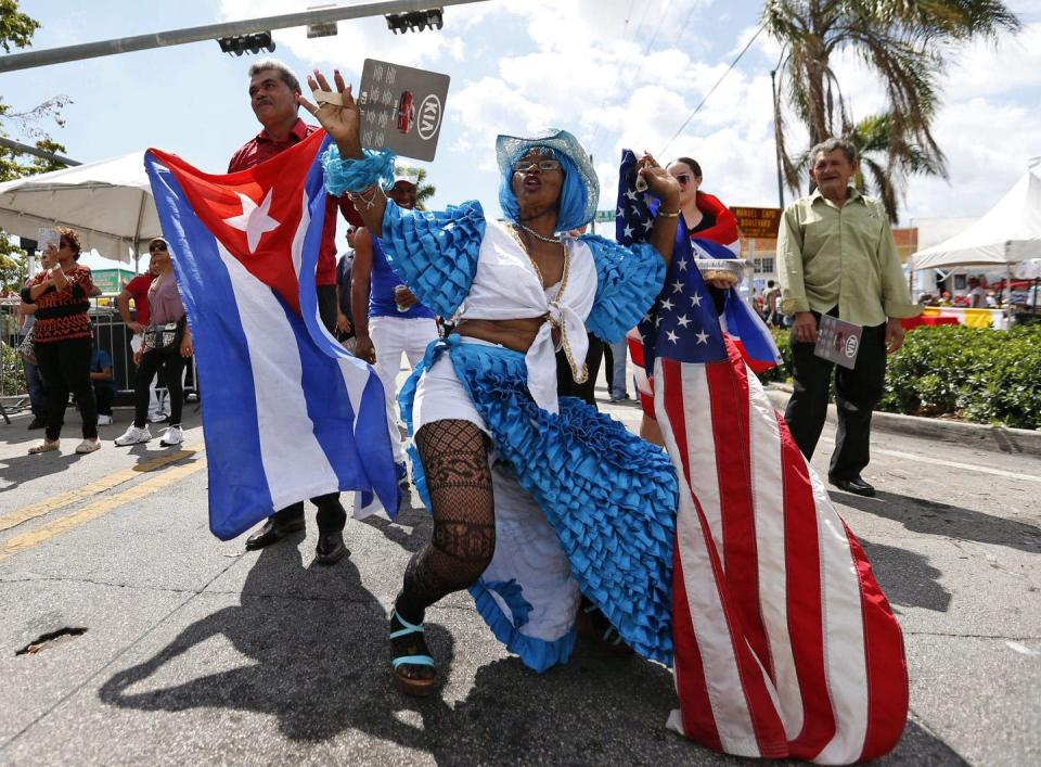 People celebrate at a festival and wave Cuban and American flags.