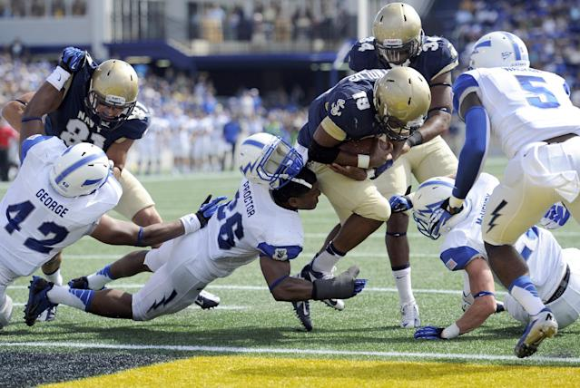 Navy quarterback Keenan Reynolds (19) scores a touchdown against Air Force linebacker Kristov George (42) and Spencer Proctor, center, and Dexter Walker (5) during the first half of an NCAA football game, Saturday, Oct. 5, 2013, in Annapolis, Md. (AP Photo/Nick Wass)