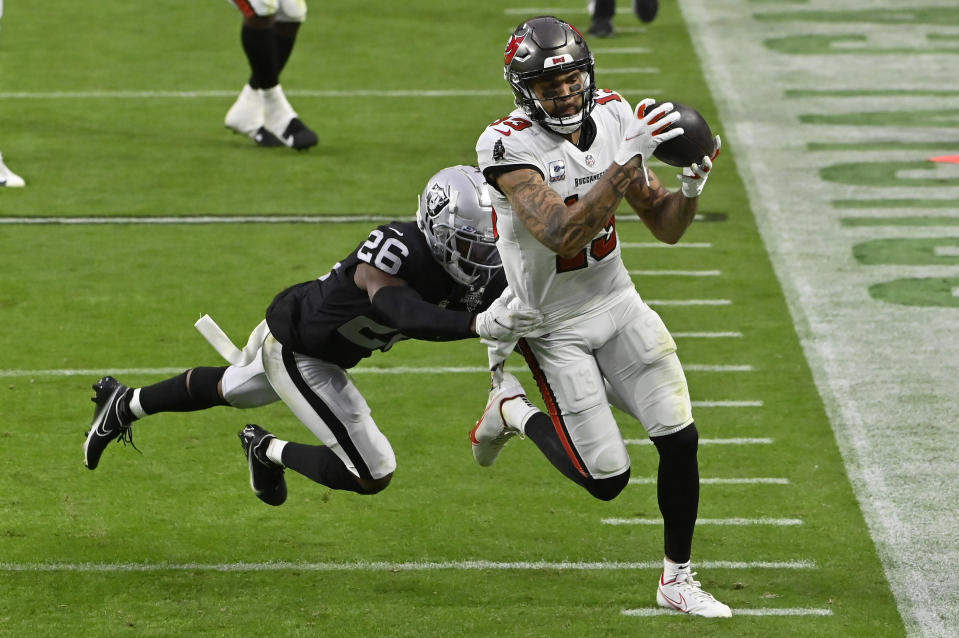 Las Vegas Raiders cornerback Nevin Lawson (26) pushes Tampa Bay Buccaneers wide receiver Mike Evans (13) out of bounds during the second half of an NFL football game, Sunday, Oct. 25, 2020, in Las Vegas. (AP Photo/David Becker)