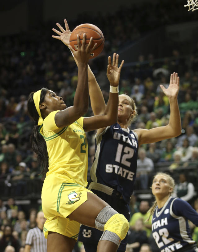 Oregon's Ruthy Hebard, left shoots next to Utah State's Hailey Bassett and Jocelyn Polansky, right, during the second quarter of an NCAA college basketball game in Eugene, Ore., Wednesday, Nov. 13, 2019. (AP Photo/Chris Pietsch)