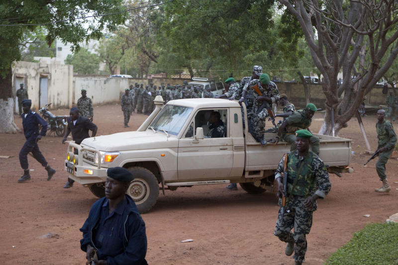 FILE - In this March 27, 2012 file photo, Malian soldiers loyal to coup leader Capt. Amadou Haya Sanogo secure the location as he arrives at his headquarters at Kati military base, just outside Bamako. A policy officer and an intelligence official have confirmed that Mali's Prime Minister Cheick Modibo Diarra was arrested at his home late on Monday, Dec. 10, 2012, by the soldiers who helped lead the recent coup. For several weeks, tension has been mounting between the soldiers who led Mali's March 21 coup and Diarra, the civilian prime minister they were forced to appoint when they handed back power to a transitional government.(AP Photo/Rebecca Blackwell, File)