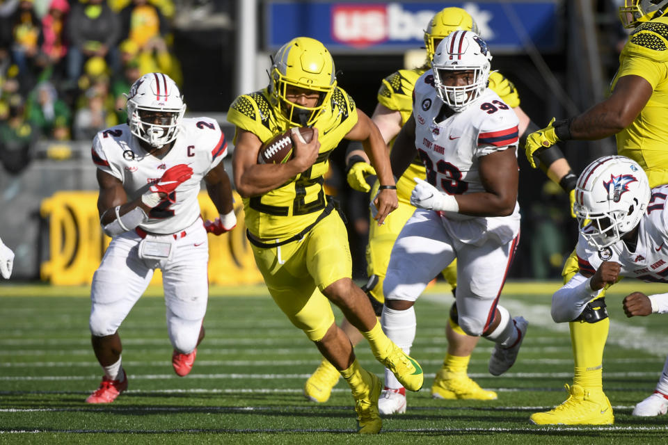 Oregon running back Travis Dye (26) runs past Stony Brook defensive lineman Casey Williams (2) and Stony Brook defensive lineman Dakar Edwards (93) during the first quarter of an NCAA college football game Saturday, Sept. 18, 2021, in Eugene, Ore. (AP Photo/Andy Nelson)