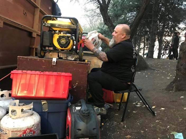 Homeless camp resident Guylain Levasseur pours fuel into one of the generators that provide electricity to a Montreal encampment set up in the summer of 2020