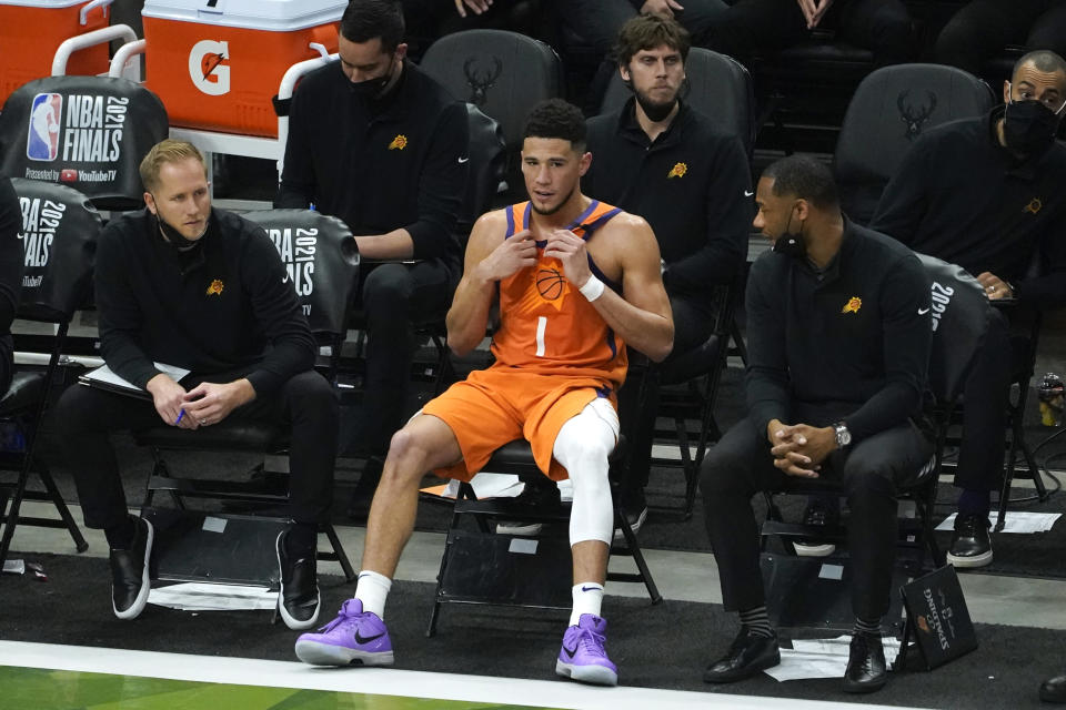 Phoenix Suns guard Devin Booker (1) sits on the bench during the second half against the Milwaukee Bucks in Game 4 of basketball's NBA Finals in Milwaukee, Wednesday, July 14, 2021. (AP Photo/Paul Sancya)