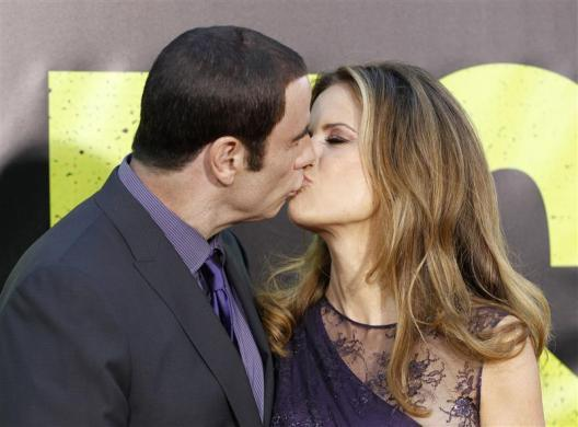 "Cast member John Travolta (L) and his wife Kelly Preston kiss as they arrive at the premiere of the film ""Savages"" in Los Angeles June 25, 2012."