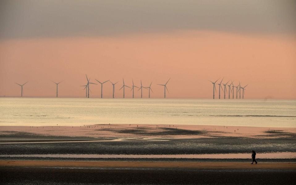 People walk on the beach at New Brighton in north west England with the Burbo Bank wind farm in the Irish Sea in the background - PAUL ELLIS/AFP