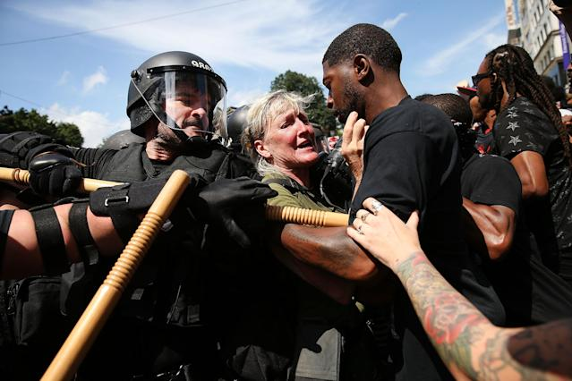<p>A photojournalist gets caught up between protesters and riot police escorting conservative activists following a march in Boston against a planned 'Free Speech Rally' just one week after the violent 'Unite the Right' rally in Virginia left one woman dead and dozens more injured on August 19, 2017 in Boston, Mass. (Photo: Spencer Platt/Getty Images) </p>