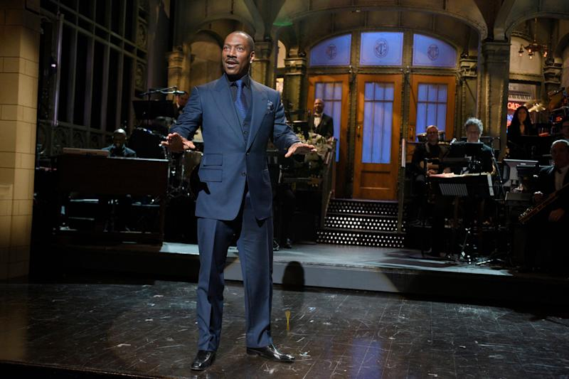Eddie Murphy stands with his arms out palms facing down on the 'SNL' stage