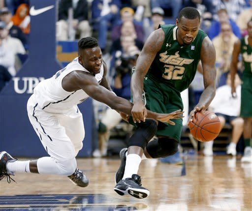 Pittsburgh's Talib Zanna, left, reaches for the ball as South Florida's Toarlyn Fitzpatrick (32) tries to control it during the first half of an NCAA college basketball game Wednesday, Feb. 27, 2013, in Pittsburgh. (AP Photo/Keith Srakocic)