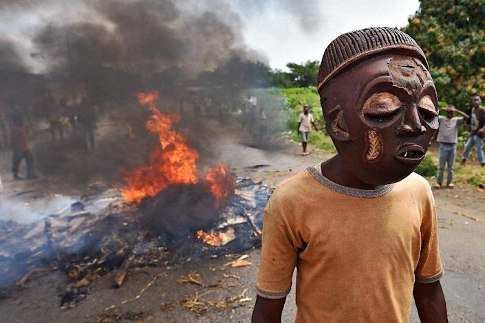 A protestor opposed to the Burundian President's third term wears a mask near a burning barricade in the Kinama neighborhood of Bujumbura on May 25, 2015 (AFP Photo/Carl De Souza)