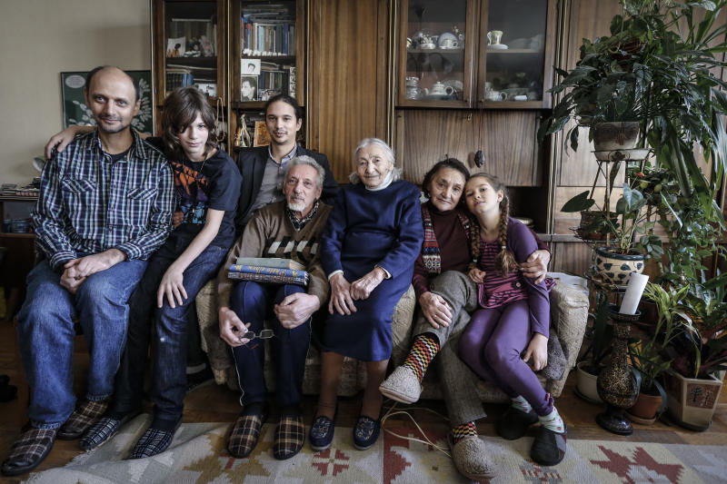 In this Sunday Nov. 11, 2012 photo from left: Mark Rozin, 47, Daniil Rozin, 11, Lev Rozin, 24, Anatoly Rozin, 78, Geda Zimanenko, 100, Luiza Rozina, 78, Maya Rozina, 8 pose in their Moscow apartment. The four generations of Zimanenko- Rozin's family embody the history of Jews in Russia over the past century, from the restrictions of czarist times to the revival of Jewish culture in Russia today. (AP Photo/Sergey Ponomarev)