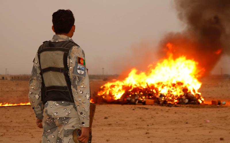 An Afghan security force member watches four tons of illegal drugs being burnt - Xinhua / Barcroft Media
