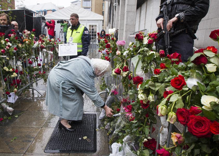 """A woman lays flowers down near the entrance the courthouse in Oslo where Anders Behring Breivik is standing trial Thursday April 26, 2012. Earlier nearly 40,000 people who turned up in poor weather at the Youngstorget square in Oslo to participate in the singing of """"Barn av Regnbuen"""" """"Children of the Rainbow"""" . The song which was a hit of Norwegian folk singer Lillebjoern Nilsen several decades ago, has become a signature tune for the victims of the July 22, 2011 bombing and shooting massacre that killed 77 people. (AP Photo/Heiko Junge / NTB scanpix) NORWAY OUT"""