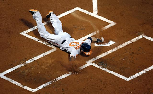 Baltimore Orioles' Manny Machado slides across the plate to score on an RBI double by Chris Davis during the first inning of a baseball game against the Boston Red Sox at Fenway Park in Boston, Wednesday, Aug. 28, 2013. (AP Photo/Elise Amendola)