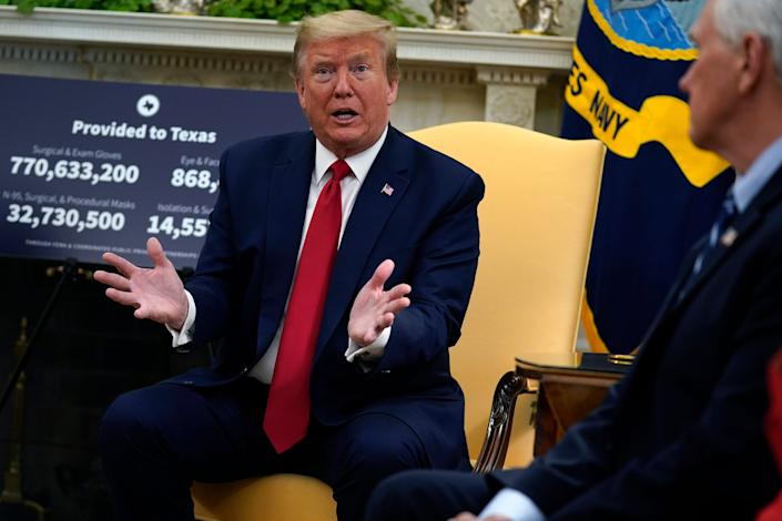 President Donald Trump speaks as Vice President Mike Pence listens at right during a meeting about the coronavirus response in the Oval Office.