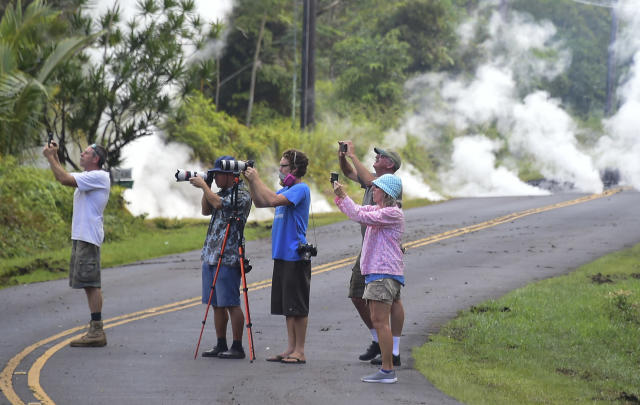 <p>People take photos of lava as steam rises from a fissure in Leilani Estates subdivision on Hawaii's Big Island on May 4, 2018. (Photo: Frederic J. Brown/AFP/Getty Images) </p>
