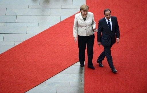 German chancellor Angela Merkel (L) shows the way to new French president Francois Hollande upon his arrival at the German Chancellery in Berlin. Merkel met Hollande Tuesday for their first-ever talks set to be dominated by differences over crisis remedies for Europe as the risk of a Greek eurozone exit piles on the pressure