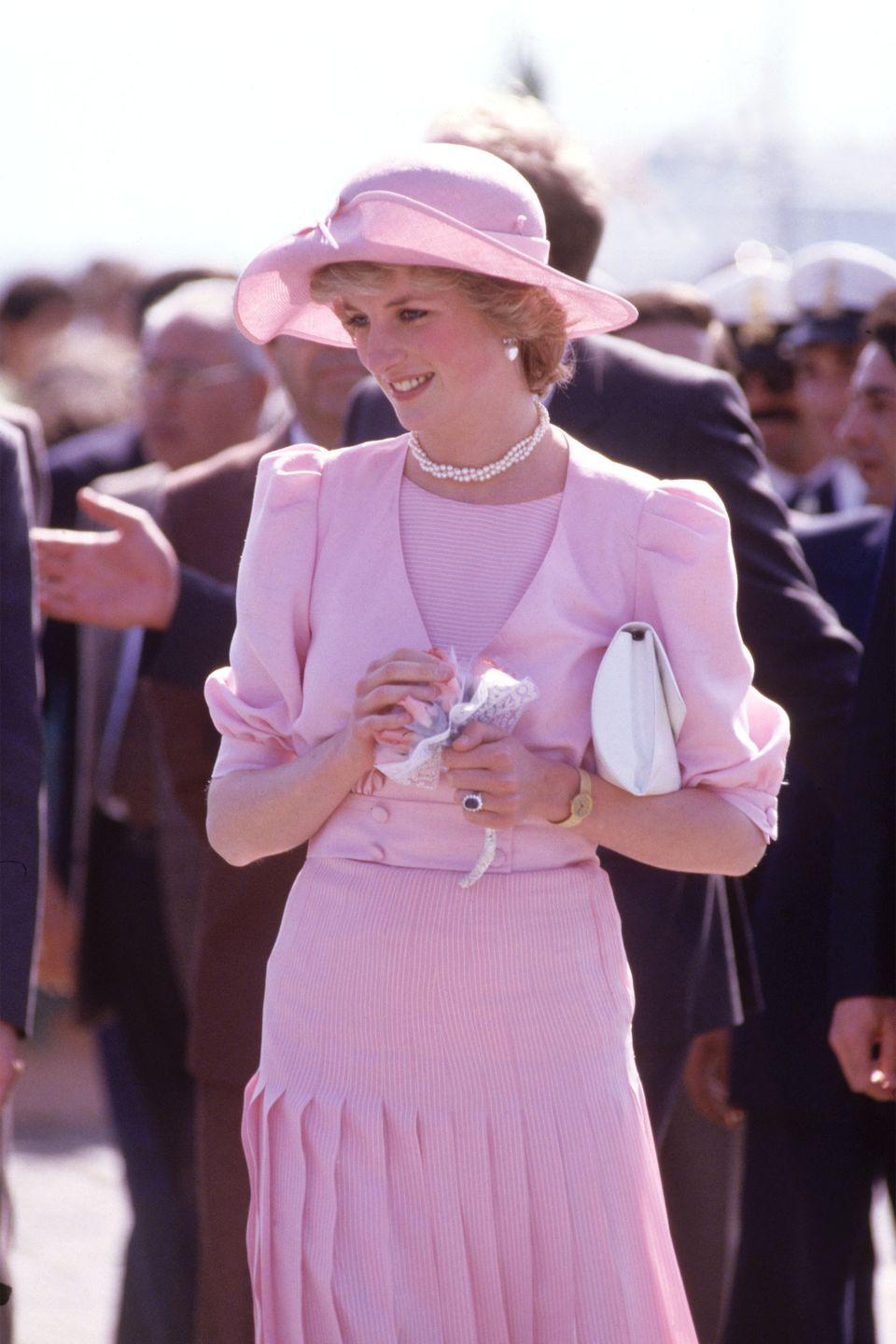 <p>In a light pink Catherine Walker look and a cap designed by John Boyd while arriving in Sicily. </p>