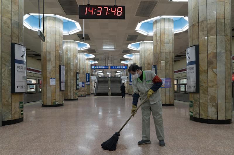 A worker cleans the floor of an empty subway station in Beijing, China.