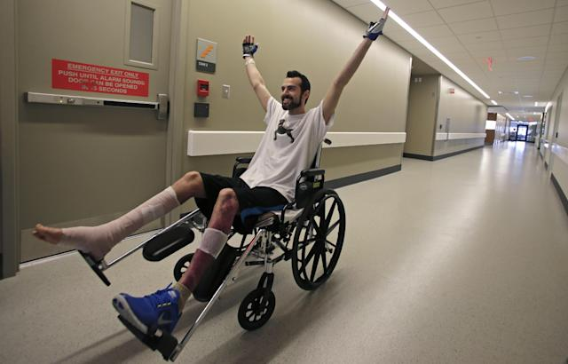 "In this Wednesday, May 22, 2013 photo, Boston Marathon bombing survivor Pete DiMartino, of Rochester, N.Y., raises his arms after completing a physical therapy session at the Spaulding Rehabilitation Hospital in Boston. DiMartino was injured in an explosion near the finish line, which blew away much of one leg and burned the other. ""I don't want anybody feeling sorry for me,"" he said. ""... I want people to see that this has made me a better person and I want people to become better people through what they see through me."" (AP Photo/Charles Krupa)"