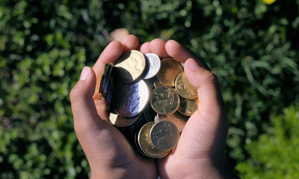 Kid's two hands full of money. Australian coins in hands showing concept of savings or wealth created.