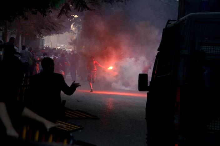 Am anti-government activist runs with a flare in Cairo, Tuesday, Nov. 26, 2013 as police disperse a protest, the security forces' first implementation of a controversial new law forbidding protests held without a permit from authorities. (AP Photo/Mohammed Asad)
