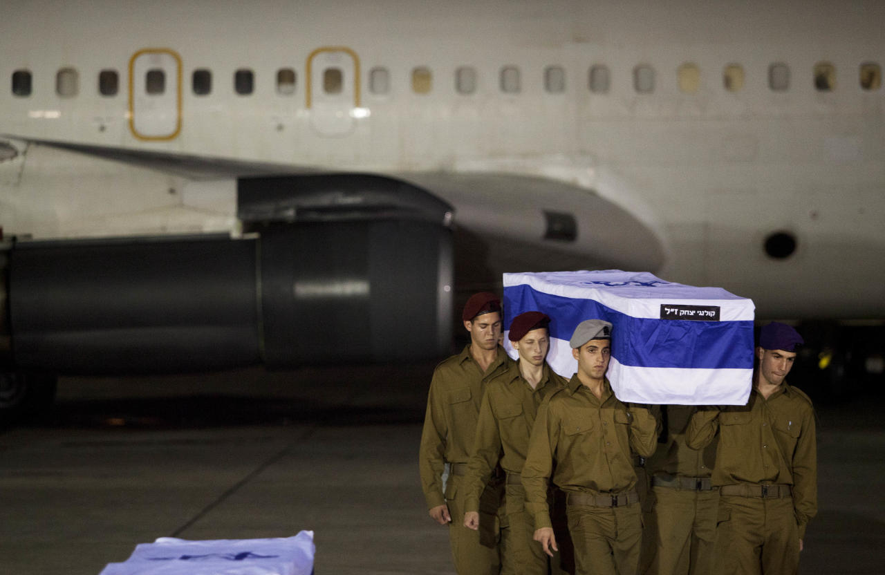 Israeli soldiers carry a coffin of victimes killed in bombing in Bulgaria after the remains arrived at Tel Aviv airport, Israel, Friday, July, 20, 2012. A man carried out a deadly suicide attack on a bus full of Israeli vacationers on Wednesday in the Black Sea resort town of Burgas, a popular destination for Israeli tourist. (AP Photo/Dan Balilty)