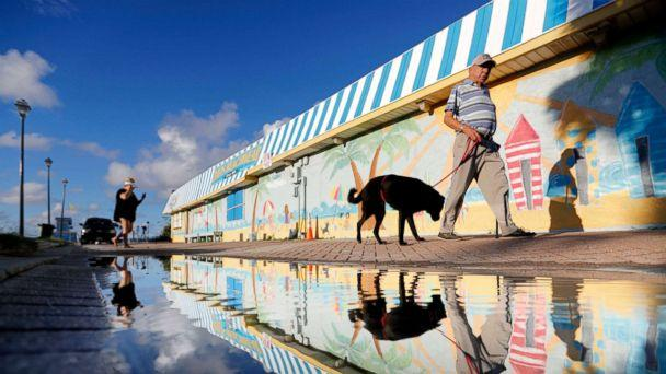 PHOTO: Beachgoers walk past a mural along the boardwalk as Hurricane Florence approaches the east coast in Atlantic Beach, N.C., Sept. 12, 2018. (David Goldman/AP)