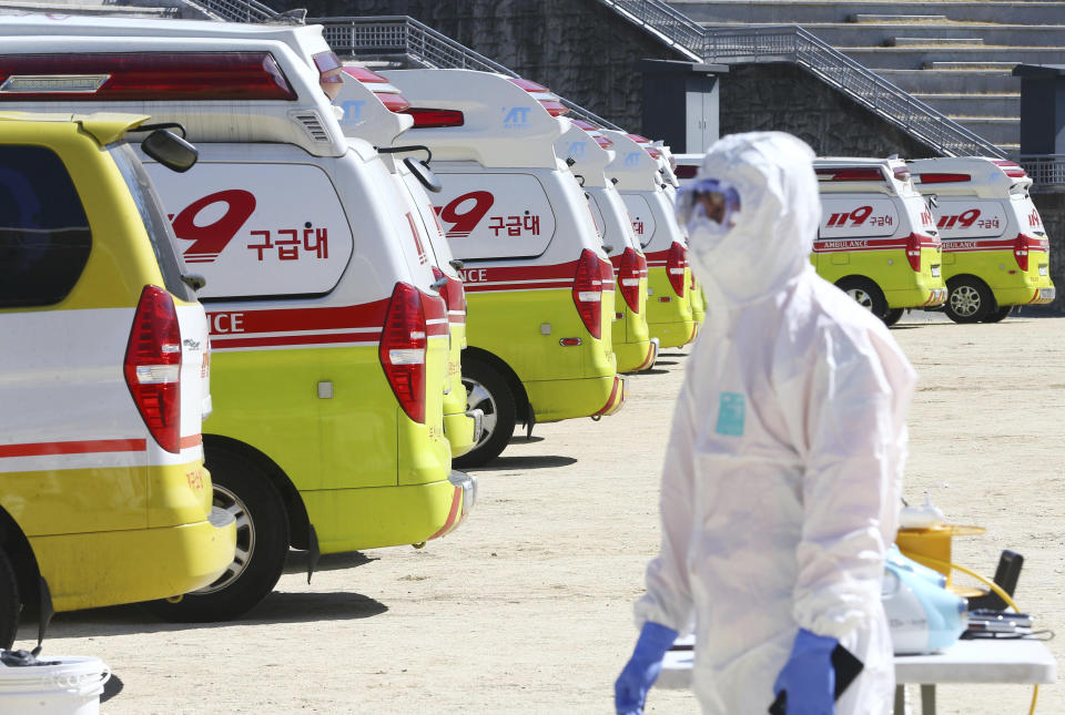 """Ambulances gather as a member of paramedic wearing protective gears walk in Daegu, South Korea, Sunday, Feb. 23, 2020. South Korea's president has put the country on its highest alert for infectious diseases and says officials should take """"unprecedented, powerful"""" steps to fight a viral outbreak. (Kim Hyun-tai/Yonhap via AP)"""