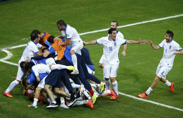 Greece's Samaras is surrounded by teammates as they celebrate his penalty goal against Ivory Coast during their 2014 World Cup Group C soccer match in Fortaleza