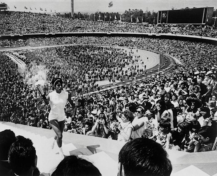 """<p>Mexican hurdler Enriqueta Basilio gets the honor of being the first woman to light the Olympic flame. The opening ceremony was viewed by over 100,000 spectators (despite the fact that the stadium <a href=""""https://bryanpinkall.blogspot.com/2012/07/1968-summer-olympic-opening-ceremony.html"""" rel=""""nofollow noopener"""" target=""""_blank"""" data-ylk=""""slk:could only hold around 63,000"""" class=""""link rapid-noclick-resp"""">could only hold around 63,000</a>). </p>"""