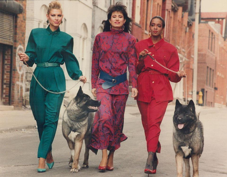 <p>Three models showcase their colorful power suits while going for a casual walk down the street. </p>