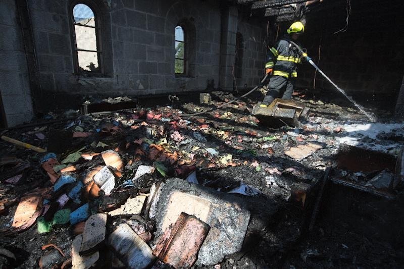 A fireman sprays water on debris in a room in the complex of the Church of the Multiplication at Tabgha in northern Israel, on June 18, 2015 in the aftermath of a suspected arson attack