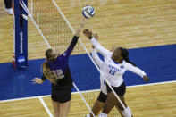Washington's Marin Grote (12) bumps the ball over Kentucky's Azhani Tealer (15) during the first set of a semifinal in the NCAA women's volleyball championships Thursday, April 22, 2021, in Omaha, Neb. (AP Photo/John Peterson)