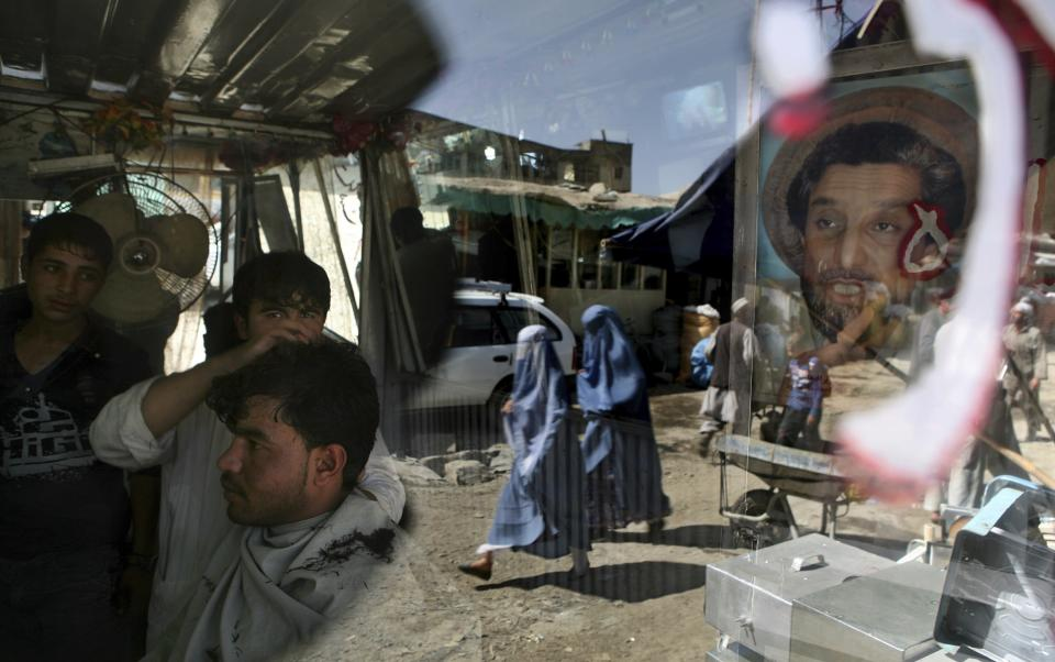 An Afghan barber works on a customer in his shop as a portrait of Afghanistan national hero Ahmad Shah Massoud adorns its door in Kabul, Afghanistan, Tuesday, Sept. 29, 2009. (AP Photo/Altaf Qadri)