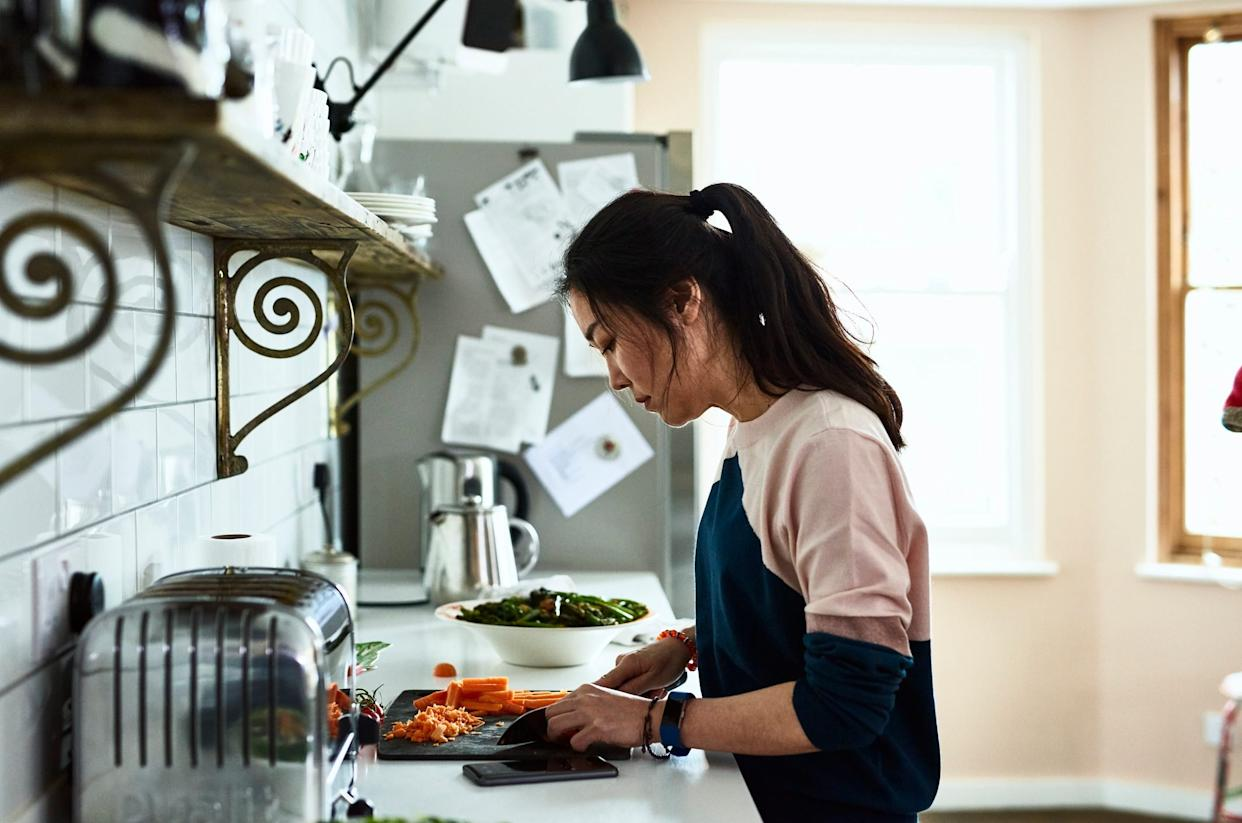 Mid adult woman chopping vegetables on kitchen counter