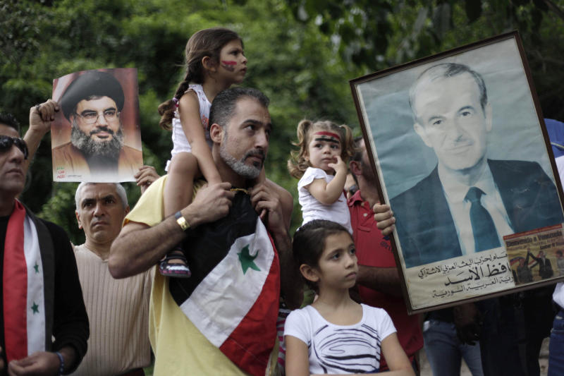 Venezuelans of Arab descent hold up photographs of Syria's late President Hafez Assad, father of Syria's current President Bashar Assad, right, and Hezbollah leader Sheik Hassan Nasrallah, left, outside the U.S. embassy in Caracas, Venezuela, Monday, Sept. 2, 2013. The demonstrators are protesting any military action in Syria by the U.S. (AP Photo/Ariana Cubillos)